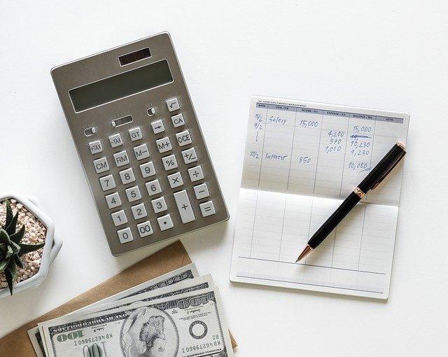 peníze, kalkulačka a papír s účty